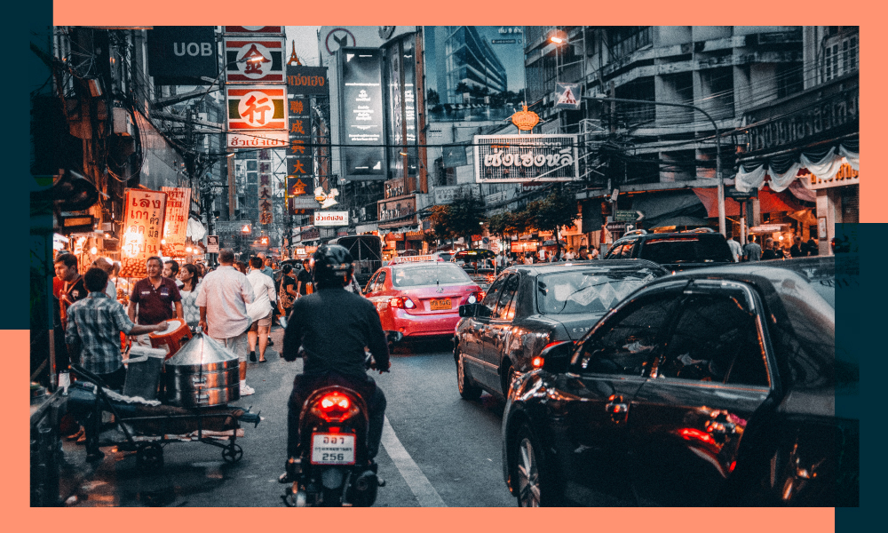 an image of a busy street in thailand with traffic and people walking against an orange border