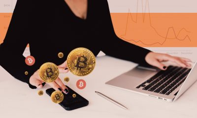Image with white and orange background, showing a woman sitting at her laptop and checking her phone that shows bitcoins and other cryptocurrency