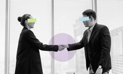 Black and white image of a woman and a man shaking hands in agreement, looking happy, in an office setting, with their eyes blocked out by colourful bars
