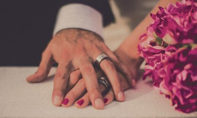 Image of a hand of a newly married man, covering the hand of his wife, next to a bunch of pink flowers