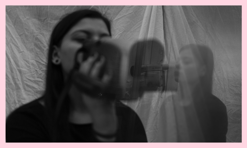 a black and white image of a woman holding a camera looking into her reflection in the mirror