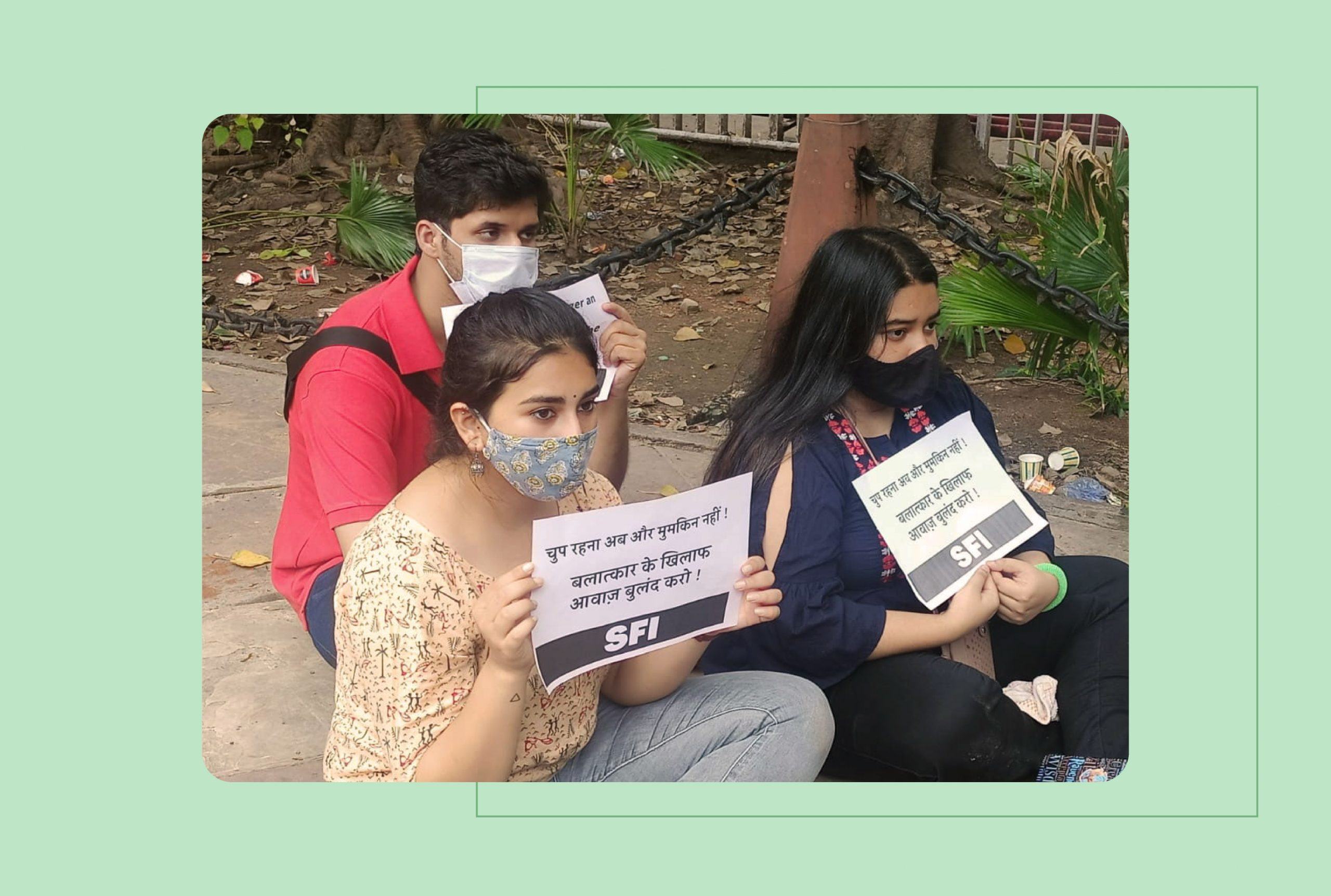 Image shows three young Indians sitting in protest with placards protesting the rape and murder of a 9 year old Dalit girl in Delhi
