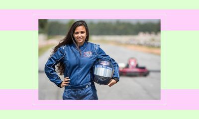 Image of Mira Erda standing on the racing track in her racing gear, with her helmet in her left hand and her right hand on her waist.