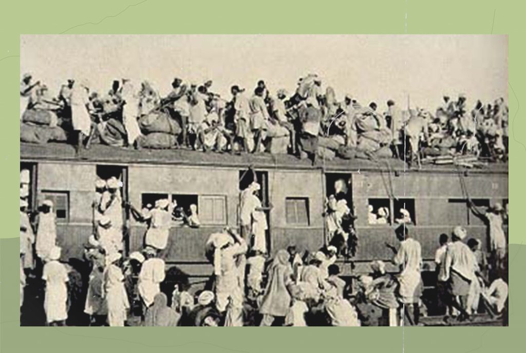 An image of an overcrowded train from 1947. People are sitting atop the train, latching on to windows and spilling over from compartments.